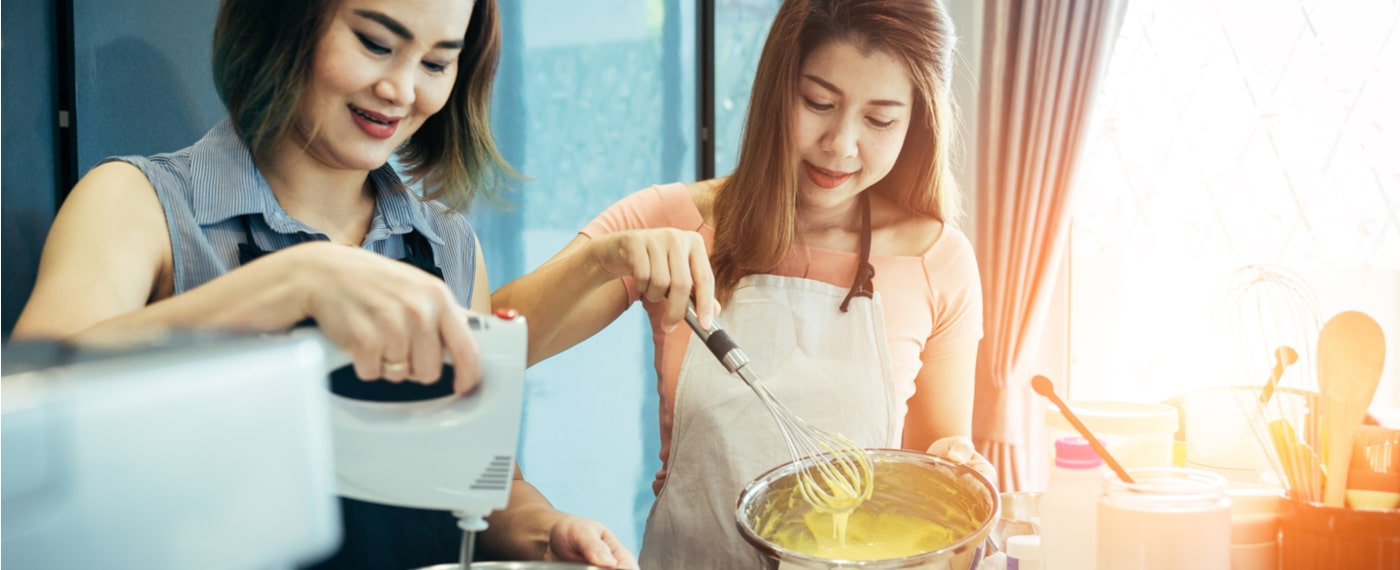two sisters whisking cake batter together while baking