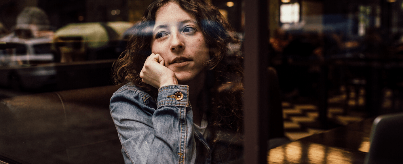 Woman staring out of restaurant window thinking about old songs