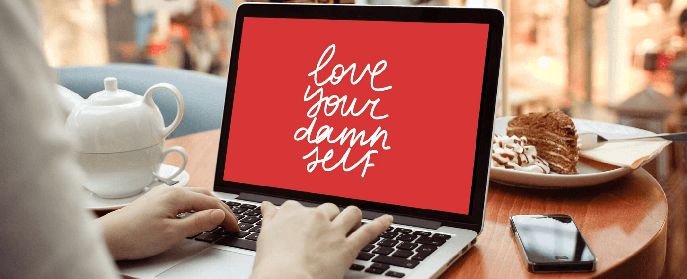 "Woman typing on a laptop screen the words ""Love Your Damn Self"""